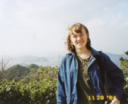 A picture of me standing on Awaji Island, Japan on a windy day with my backpack and blue jacket.